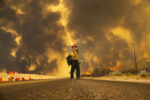 2. A firefighter reports that the Blue Cut fire is burning on both sides of Highway 138 in Phelan, CA. (Gina Ferazzi / Los Angeles Times)
